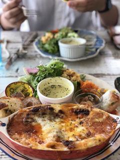 食べ物の皿を持ってテーブルに座っている人々のグループの写真・画像素材[2298859]