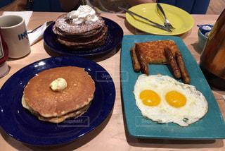 テーブルの上に食べ物のプレートの写真・画像素材[1147230]