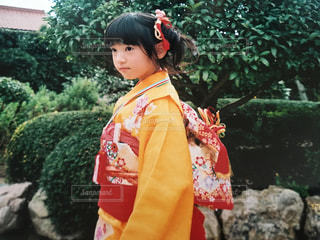 茂みの前に立っている赤いドレスを着た少年の写真・画像素材[859056]