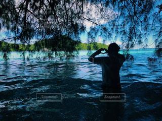 水の体の横に立っている人の写真・画像素材[754677]