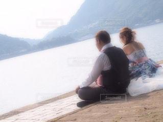 水の体の横に座っている人 - No.788420