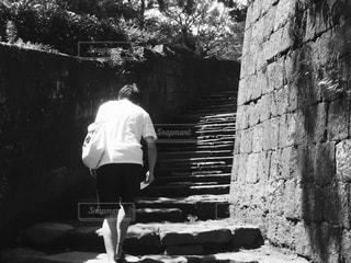 レンガ壁の前に立っている男の写真・画像素材[817349]