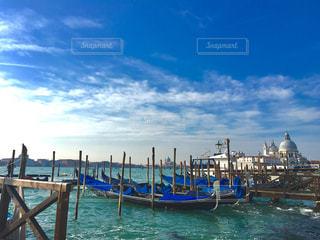 水の体の横に座っている青と白のボートの写真・画像素材[1194657]