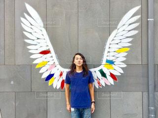 建物の前に立っている間凧をもつ少女の写真・画像素材[750240]