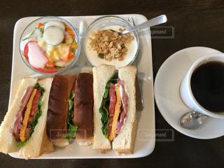 テーブルに食べ物のプレートの上に座ってサンドイッチの写真・画像素材[1078591]
