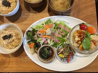 テーブルの上の皿の上に食べ物のボウルの写真・画像素材[1288449]