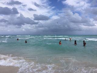 水の体の近くのビーチの人々 のグループの写真・画像素材[1385242]