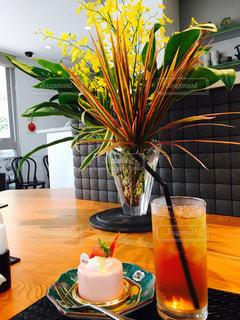 テーブルの上の花の花瓶の横にあるオレンジ ジュースのガラスの写真・画像素材[807516]