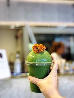 近くに緑のボトルを保持している人のの写真・画像素材[1411510]