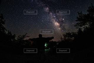 暗い空に立っている人の写真・画像素材[2132508]