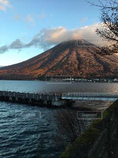 背景の山が付いている水の体の上の橋の写真・画像素材[783864]