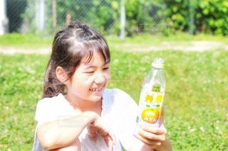 草の上に座ってジュースを飲んでいる女の子の写真・画像素材[2225430]
