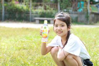 公園でジュースを飲んでいる女の子の写真・画像素材[2226326]