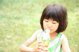 公園でジュースを飲んでいる女の子の写真・画像素材[2226631]
