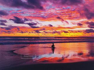 ビーチで夕日を背景にした人の写真・画像素材[2833746]