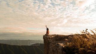 丘の上に座ってる人の写真・画像素材[3834984]