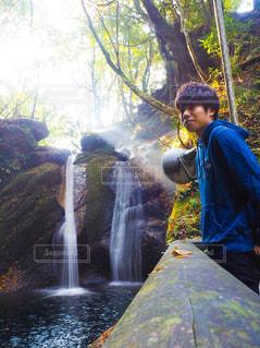 滝の隣に立っている男 - No.868991