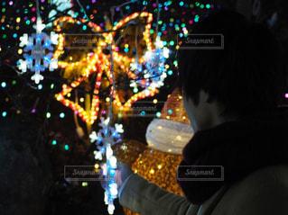 夜ライトアップされたクリスマス ツリーの周りに座って人々 のグループ - No.926902
