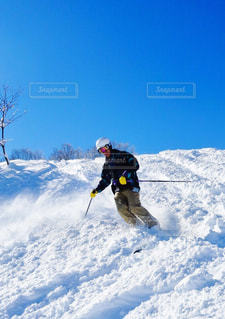 雪に覆われた斜面をスキーに乗る男の写真・画像素材[934162]