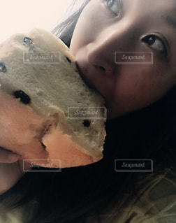 近くにドーナツを食べる女性のアップの写真・画像素材[706132]