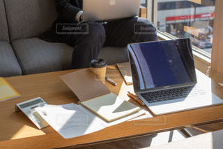 ラップトップコンピュータを使ってテーブルに座っている人の写真・画像素材[2963123]