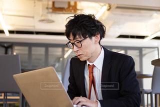 スーツを着て、机に座っているネクタイを締めた男性の写真・画像素材[2969708]