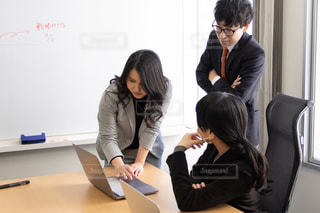 ノートパソコンの画面を見ながら話す男女3人の写真・画像素材[2974438]