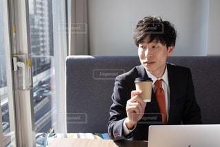 ラップトップの前に座っているスーツとネクタイを着た男の写真・画像素材[2974441]