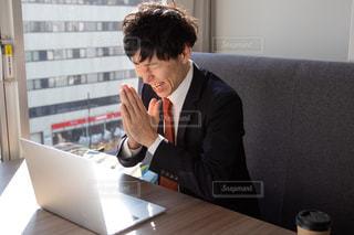 ノートパソコンの前で祈る男性の写真・画像素材[2974445]
