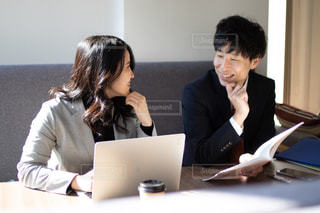 パソコン作業をしながら談笑する男女2人の写真・画像素材[2974452]