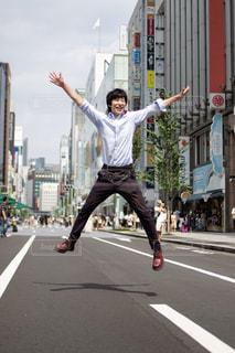 街の通りで両手を広げてジャンプする男性の写真・画像素材[2984958]