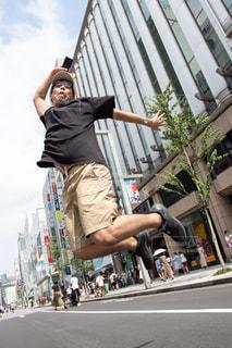 街の通りでジャンプしている男の写真・画像素材[2985020]
