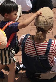 子供の隣に立っている少年の写真・画像素材[2513957]
