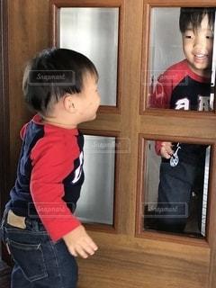 窓の前に立っている小さな男の子の写真・画像素材[2697567]
