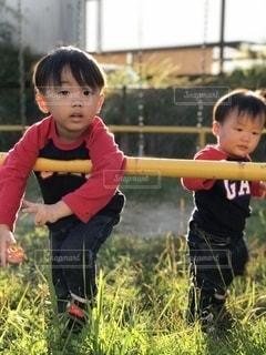 草の中に立っている小さな男の子の写真・画像素材[2697910]