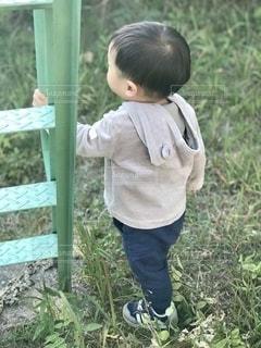 草の中に立っている小さな男の子の写真・画像素材[2708650]