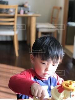 テーブルを背に遊ぶ男の子の写真・画像素材[2734306]