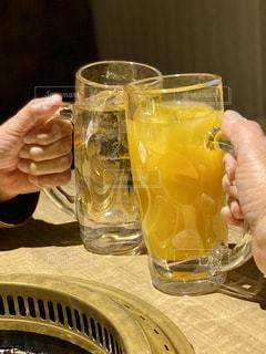 2人,ジュース,手,ガラス,テーブル,人物,人,イベント,グラス,カップ,乾杯,ドリンク,パーティー,ジョッキ,オレンジジュース,ジンジャエール,握る,手元,飲料,飲む,ソフトドリンク