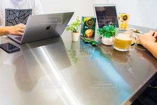 ノート パソコンでテーブルに座っている人の写真・画像素材[1292645]