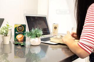 ラップトップを使用してテーブルに座っている女性の写真・画像素材[1292661]