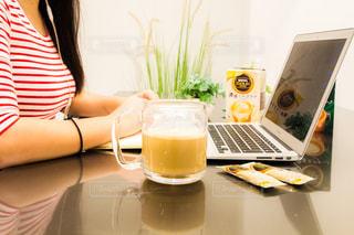 ラップトップを使用してテーブルに座っている女性の写真・画像素材[1292721]