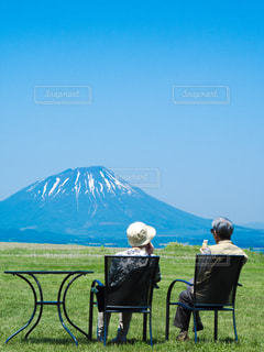 山の前に座っている椅子夫婦の写真・画像素材[1457167]