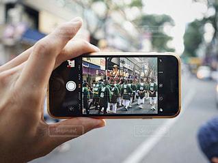 近くに携帯電話を持つ手のアップ渋谷のお祭りの写真・画像素材[1460746]
