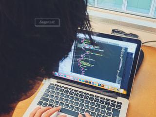 ラップトップ コンピューターの前に座ってプログラミングしてる人の写真・画像素材[1525405]