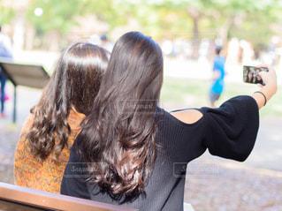 公園のベンチで自撮りしている二人の女性の写真・画像素材[1591048]