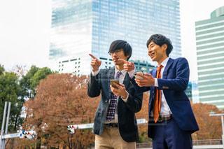 携帯電話で話している建物の前に立っている男の写真・画像素材[1666908]