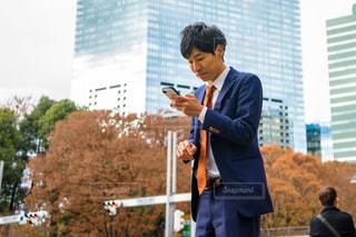 携帯電話で話している建物の前に立っている男 スマホをいじる男の写真・画像素材[1666909]