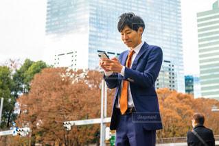 携帯電話で話している建物の前に立っている男 携帯をいじる男の写真・画像素材[1667014]