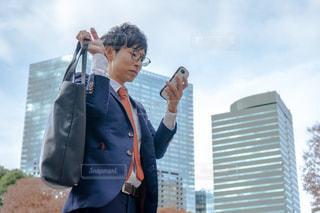 建物の前に立っている人 携帯をいじるビジネスマンの写真・画像素材[1667079]