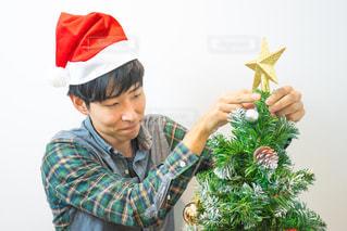 クリスマスツリーの飾り付けをする男性の写真・画像素材[1670974]